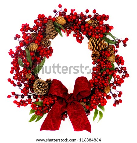 A brown twig wreath is decorated with red  berries, pine cones and a red damask bow.