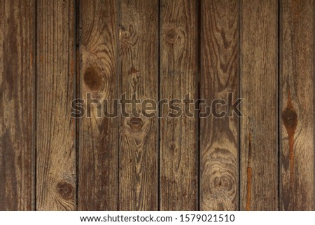 A brown wooden fence (or background, floor, wall) of rough planks or planks with a wood texture and knots.