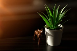 A brown wooden figurine of a deer and a plant in a pot. Blurred sun glare. Beautiful background, warm spring wallpaper.
