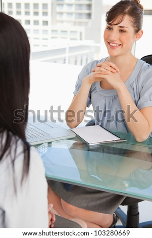 A brunette business woman chats with her other co worker