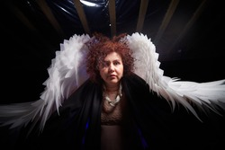 A brunette curly girl in black dress looking like an evil angel with white wings on a black background. Model and actress posing in the studio
