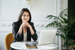 A brunette financier in a business suit. Sitting in a comfortable chair and reading an electronic textbook on a laptop. The student studies the basics of economics. Online training in a cafe.