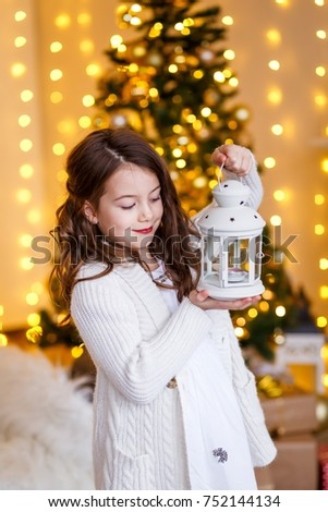 A brunette gilr in front of fur-tree and fireplace with candles and gifts. A surprised girl. A girl dreaming. New year's eve. Christmas eve. Cozy holiday at the fur-tree with lights and gold decor. #752144134