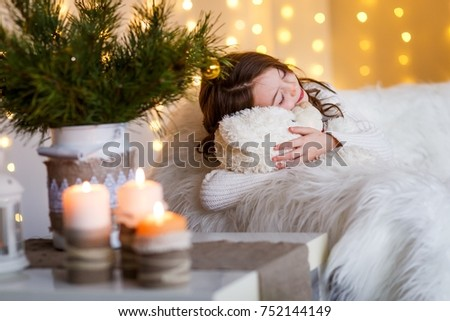 A brunette gilr in front of fur-tree and fireplace with candles and gifts. A surprised girl. A girl dreaming. New year's eve. Christmas eve. Cozy holiday at the fur-tree with lights and gold decor. #752144149