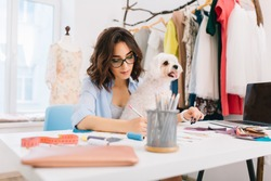 A brunette girl in a blue shirt is sitting at the table in the workshop . She is deawing some sketches. The dog is sitting on the knees.