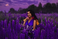 A brunette girl in a gradient haute couture dress in blue, pink and yellow colors standing among a blooming lupine field. A magical romantic night portrait.