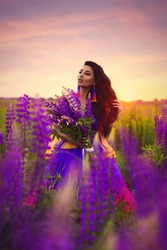 A brunette girl in a gradient haute couture dress in blue, pink and yellow colors standing among a blooming lupine field. A magical romantic sunset portrait.
