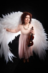 A brunette girl in an elegant dress, with violin and white angel wings on a black background. Model, violinist, actress posing in the studio