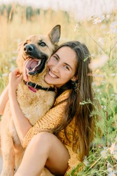 A brunette girl is sitting on the grass and hugging with a German shepherd dog in the meadow. Sunset and blurred background on backdrop. The concept of nature walks on vacation. Laughter and emotions.