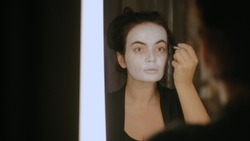 A brunette girl with a white face draws a circle around her eyes with black eyeliner, looking at her reflection in the mirror. Halloween makeup. October holiday.