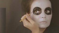 A brunette girl with a white tone on her face brightens the black circle around the eye with a thin brush. Close-up. Halloween makeup. October holiday.