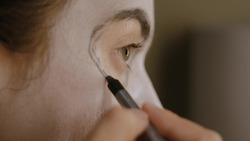 A brunette girl with white paint on her face paints the round area around the eye with black pencil. Halloween makeup. Close-up of the face and hands.