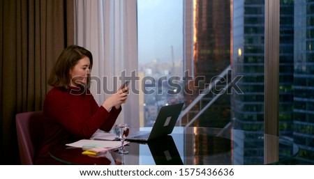 a brunette in a Burgundy dress sits at a round table near a large window. she holds a smartphone in her hand and communicates via video link. behind the window you can see high-rise city buildings #1575436636