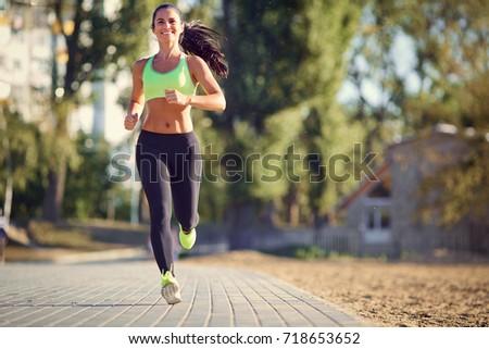 A brunette runner woman runs in the park jogging.