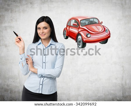 A brunette woman is teaching a basis of road traffic regulations. A sketch of a red car is drawn on the concrete wall.