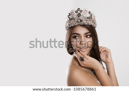 A brunette woman looking back, crown on head smiles and looks backwards touching face with hand showing crystal diamond ring jewelry on white gray. Multicultural ethnic model mixed race indian african