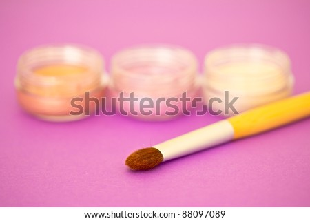 a brush and some eyeshadow on pink background