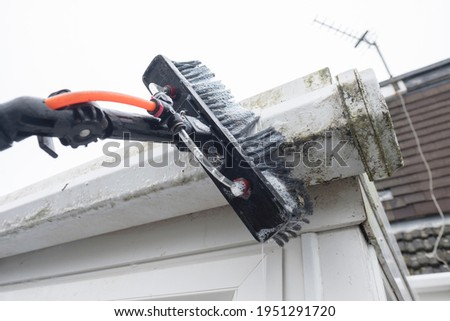A brush cleaning dirty clogged white plastic pvc gutters and drain pipes with mossy green mould plastic fascias.  Blocked drains and guttering need window cleaners and regular yard work maintenance  Photo stock ©