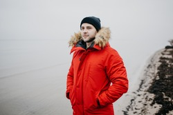 A brutal man with a beard in the red parka, black cap, and blue jeans stands on the beach and looks at the sea. A sailor in a parka on the shore waiting for a ship. Jurmala Latvia.