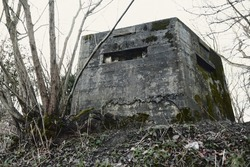 A brutalist cold gritty concrete world war two, ww2 pillbox war bunker defence fortress in a dirty forgotten woodland in europe. wartime relics and forgotten outpost using solid architecture to defenD