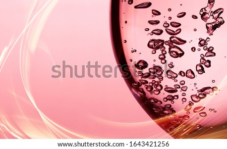 Photo of  A bubble splash of transparent clear water liquid in glass at sunlight.