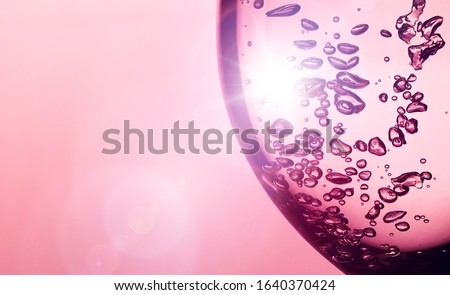 Photo of  A bubble splash of transparent clear water liquid in glass at sunlight. holiday light background. holiday postcard background. wineglass with bubbles