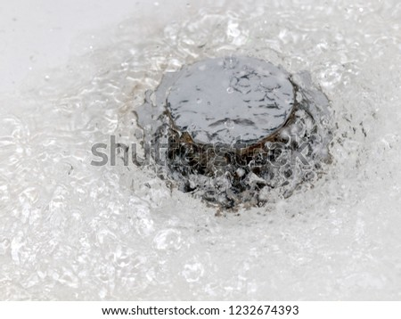 a bubbling with air bubbles a strong stream of water flows into the manhole #1232674393