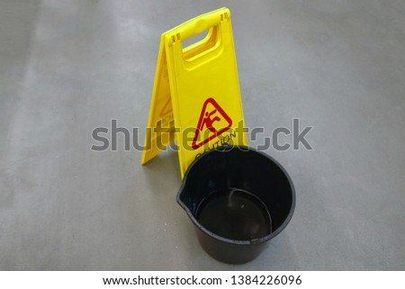 A bucket of water and a sign - carefully slippery floor. Copyspace for lettering. Caution can slip, the floor is slippery.
