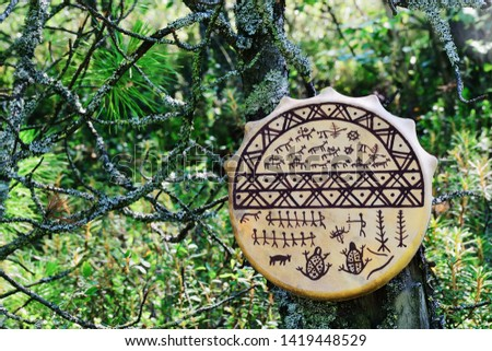 A buckskin tambourine with pictograms hangs on an old tree covered with moss. In the background, the autumn vegetation of the tundra. Negative field. Close up. Blurred background. #1419448529