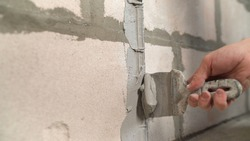 A builder applies plaster with a trowel to a concrete wall to anchor the metal building beacon. The builder applies the plaster with a trowel.