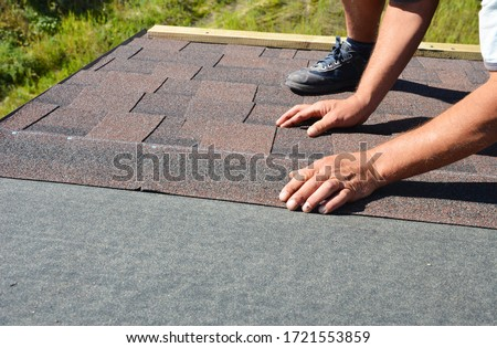 A building contractor is installing  dimensional asphalt roof shingles on the underlayment of the house construction repairing the rooftop.