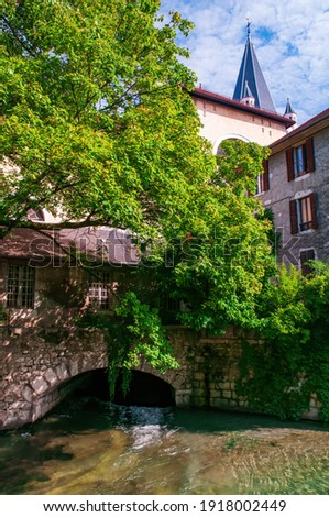 A building on a canal bridge in the city centre of Annecy, France near Jardin de l'Eveche with Eglise Notre Dame de Liesse in the background Photo stock ©