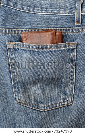 A bulky wallet on a jeans pocket, a concept of wealth