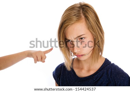 A bully pointing her finger at a girl wearing headgear