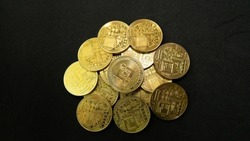 a bunch of bitcoin gold coins piling up and scattering with black background