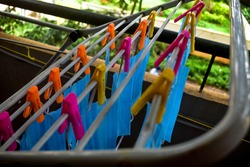 A bunch of blue colored face masks are being hanged on a cloth rod for drying purpose after cleaning them for reuse. Reusable masks with clips hanged on a wire