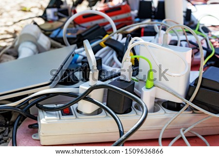 a bunch of charging gadgets, electronic devices, messy wires. dependence on electricity #1509636866