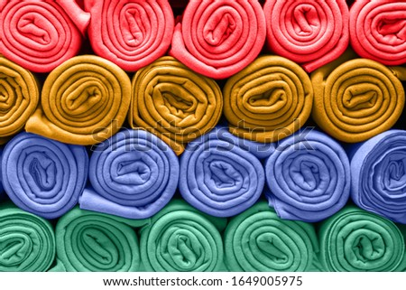 A bunch of colorful blankets folded in rows. Rolls of colored rugs lie on a shelf, texture effect. Photo stock ©