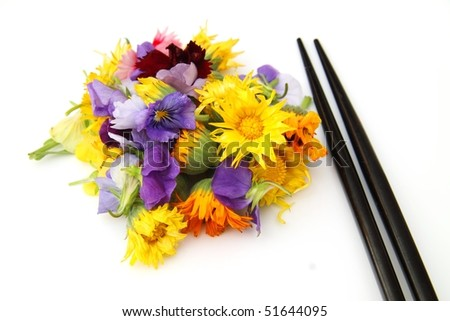A bunch of edible flowers with a pair of chopstick at the side, isolated over white