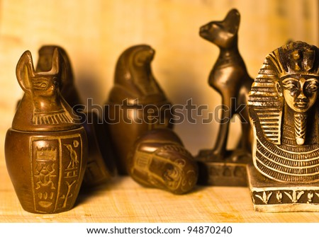 A bunch of egyptian figurines over papyrus paper background, selective depth of field.