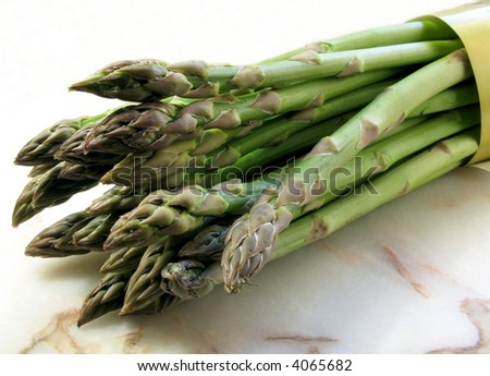 A bunch of fresh asparagus on a marble table