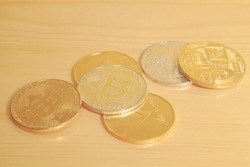 A bunch of golden virtual currency coins (Bitcoin, Ethereum) on a wooden table.