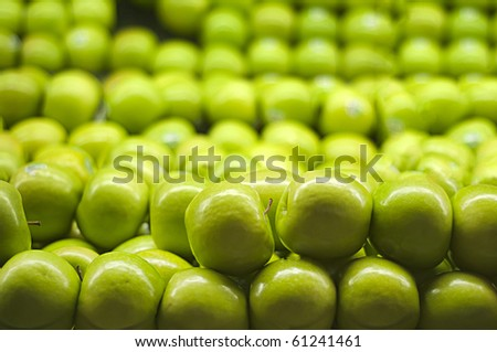 A bunch of green apples piled up at the supermarket.
