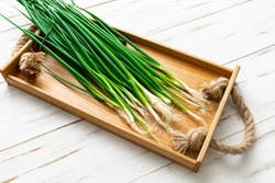 A bunch of green onions on a light wooden background.