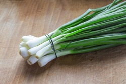 A bunch of green onions on a table close