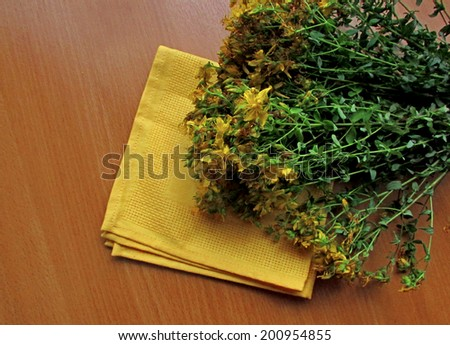 A bunch of herbs lies on the wooden table