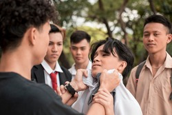 A bunch of high school delinquents bully a smaller boy. One bully grabs him by the collar. Emotional and physical abuse issues in teenagers.