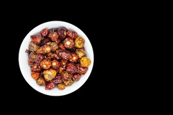 a bunch of hot round chillies in a white bowl in black background, Selective focus, Selective focus on subject, background blur