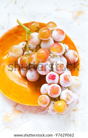 A bunch of icy frosted grapes - muscat variety.  Top view of grapes on a vintage orange plate.