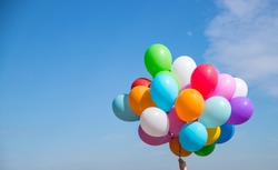 A bunch of multicolored balloons with helium on a blue sky background
